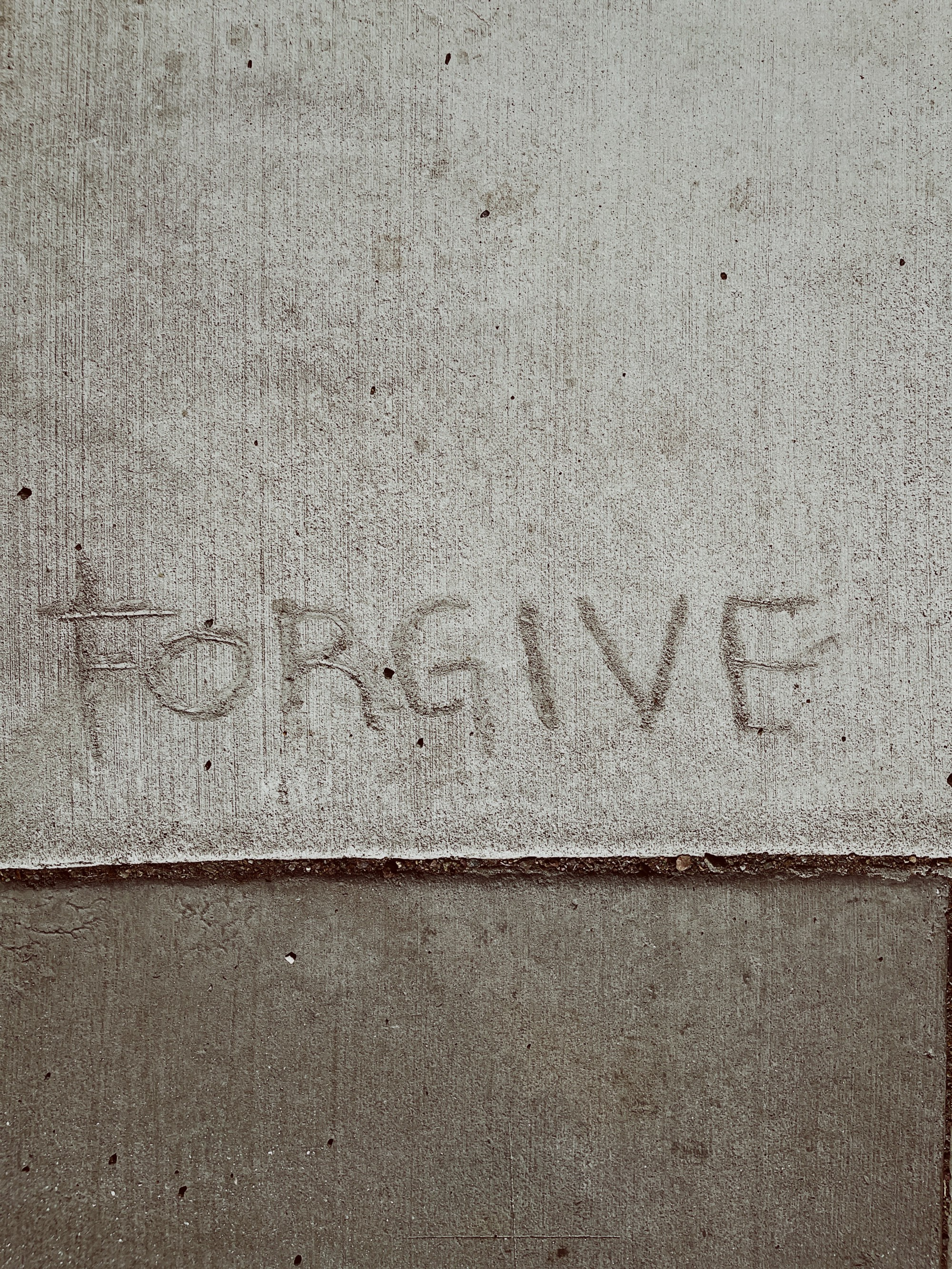 The word forgive written in a cement sidewalk