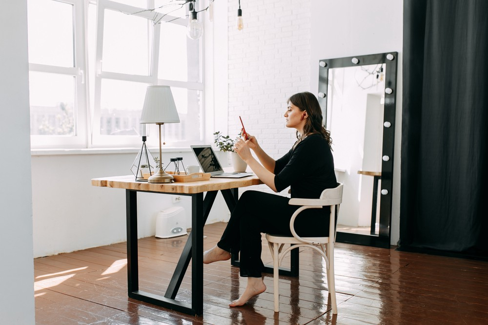 Woman holding a mobile phone, wearing casual clothes working from a home office using a laptop.
