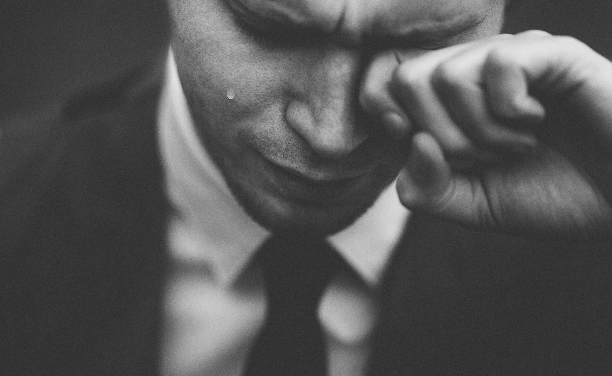 A man in suit is crying, close up face shot, showing a tear falling down on his right cheek, while he rubs his left eye.