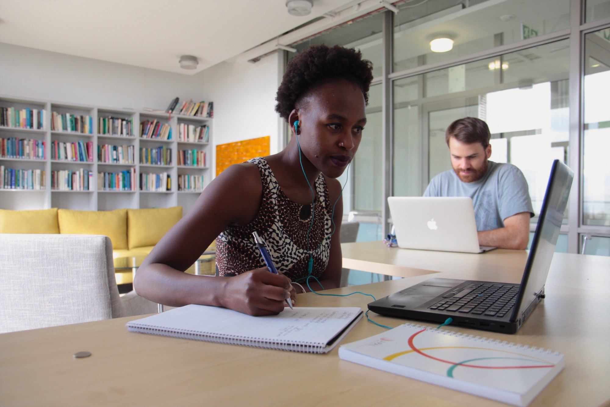 African woman taking notes in a notebook while watching a video on her laptop. White male working on laptop in the background.