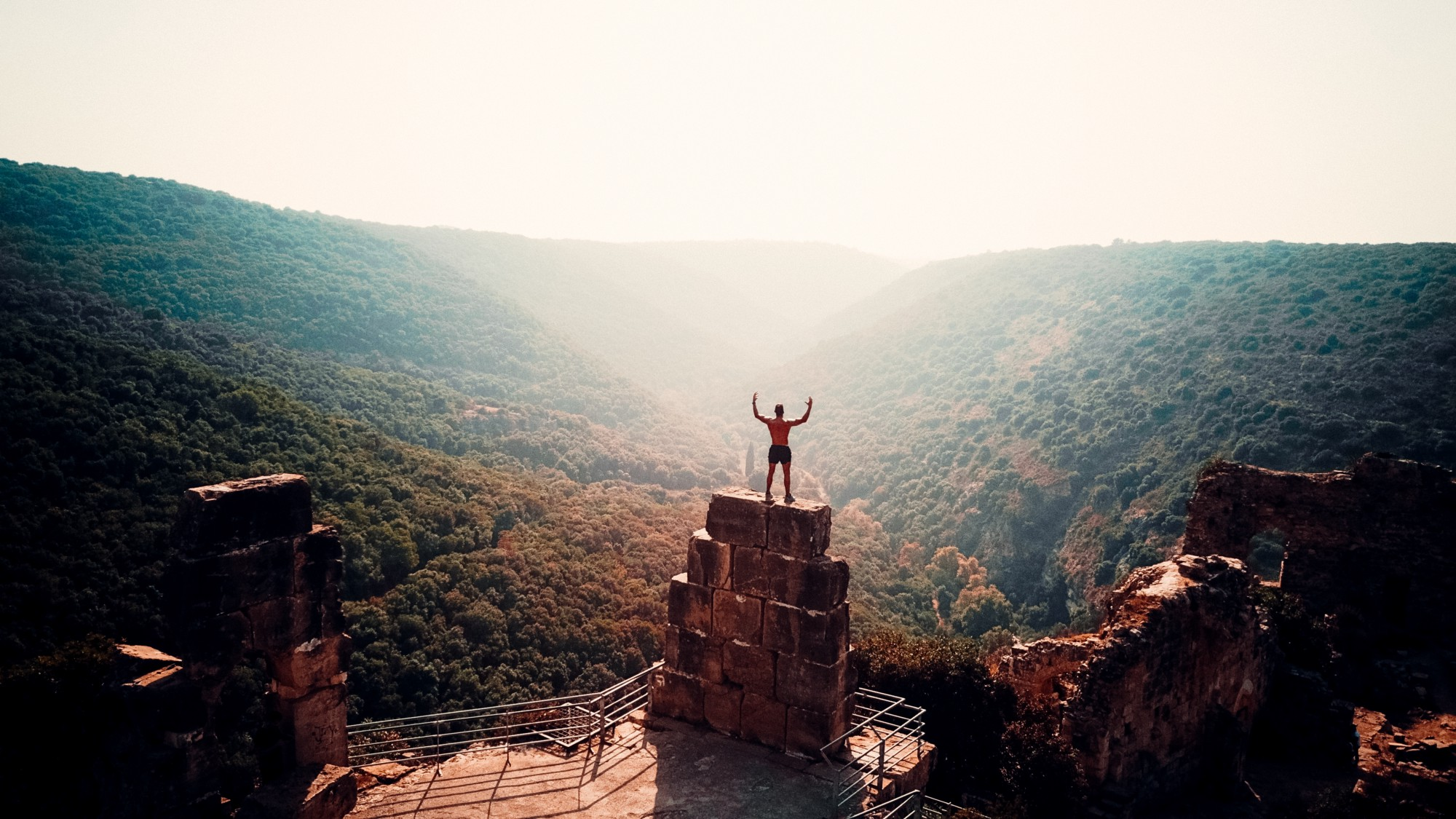 Man standing on top of pillar with arms outstretched. Mountains in the background.