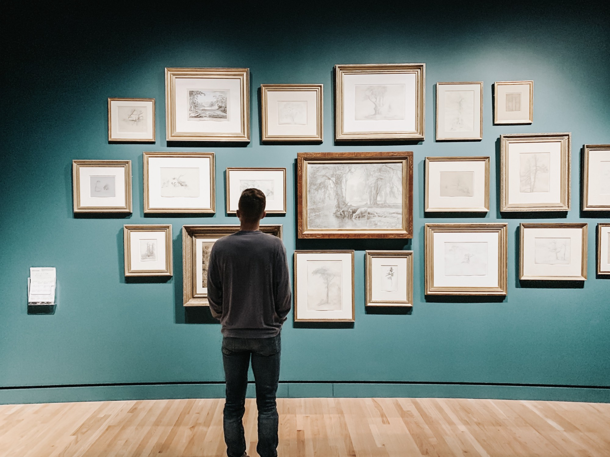 Man looking at framed artworks on a wall.