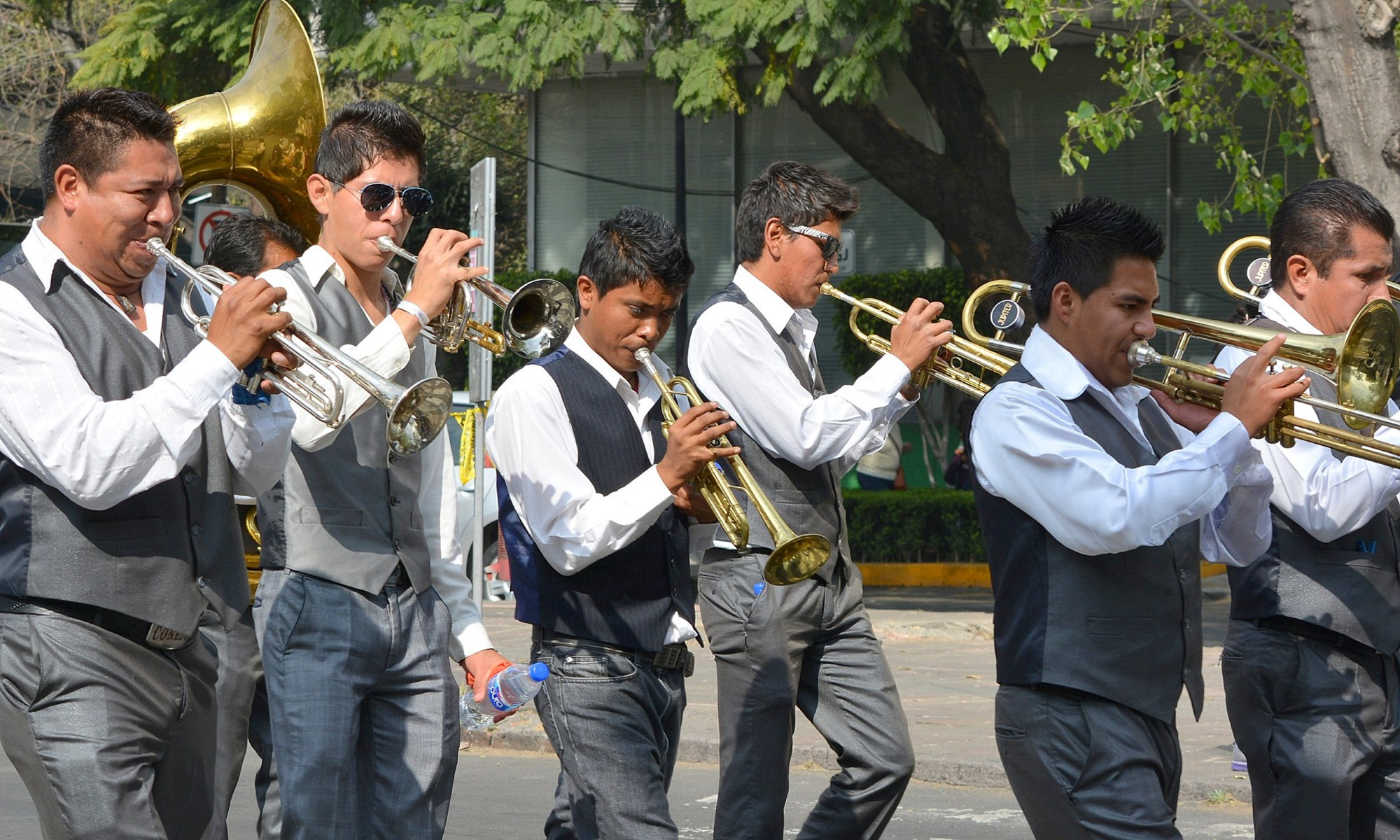 6 marching trumpet players in gray vests and slacks