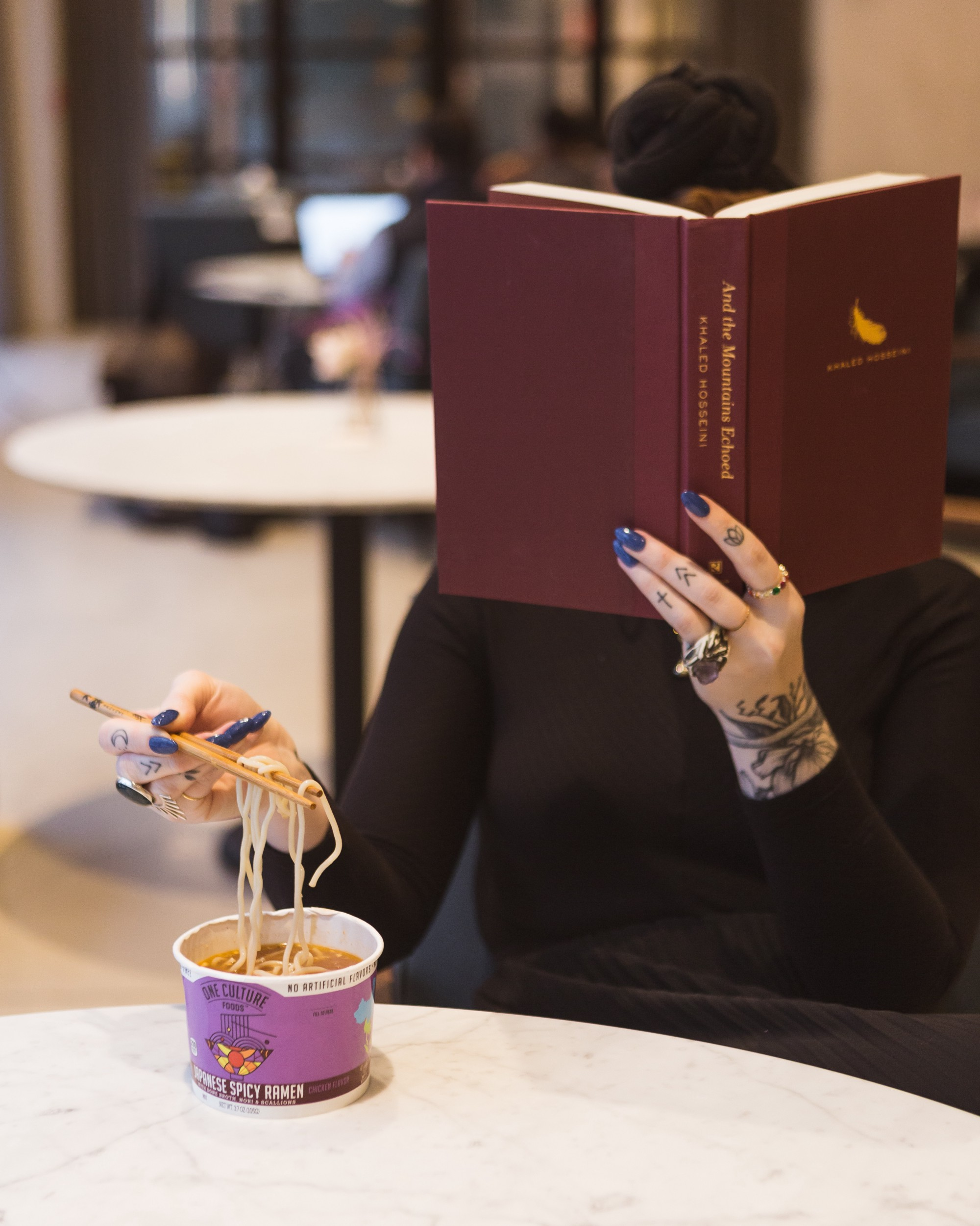 A woman trying to eat and read at the same time