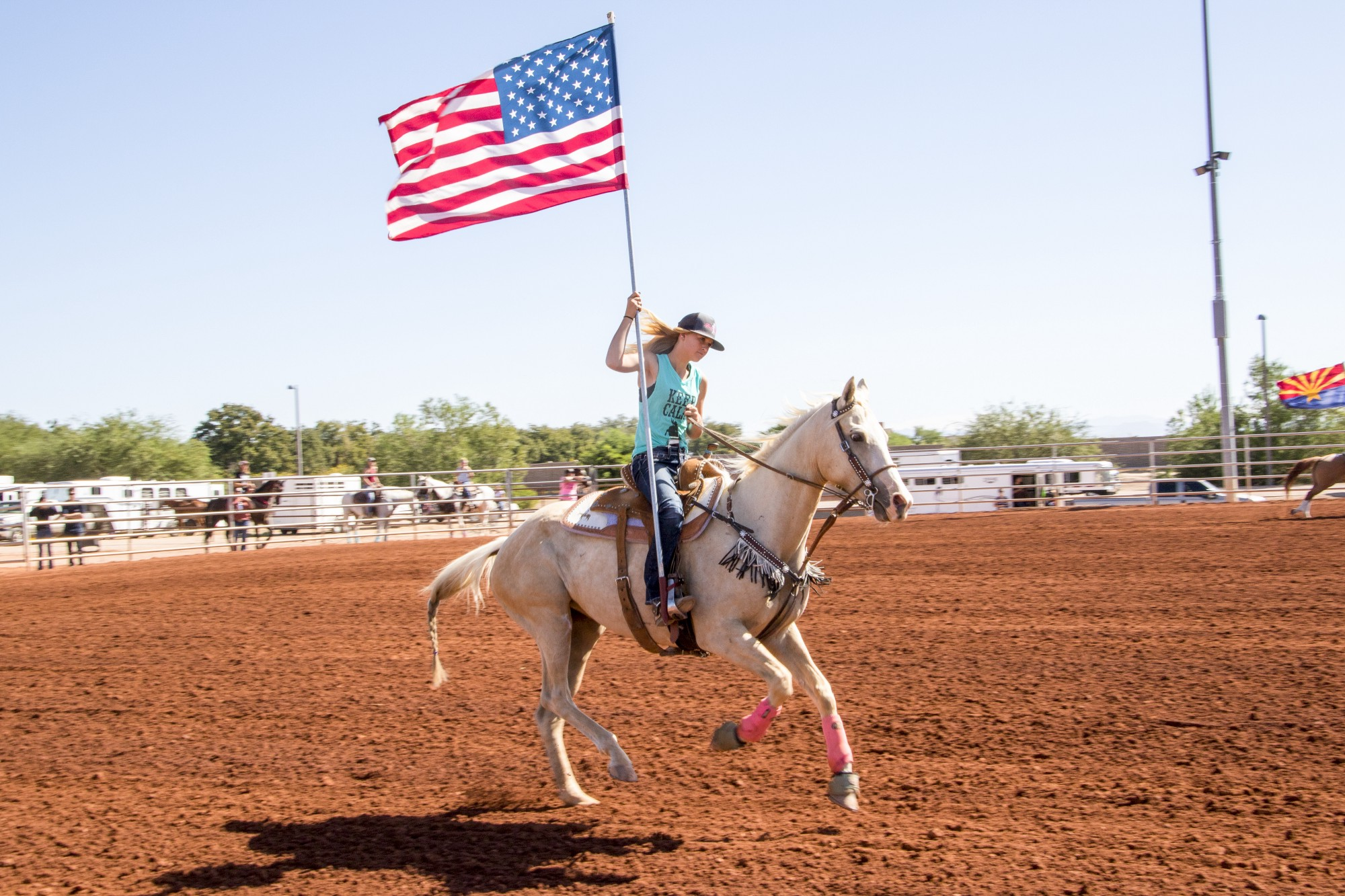 rodeo queen in the ride up, carrying an American flag