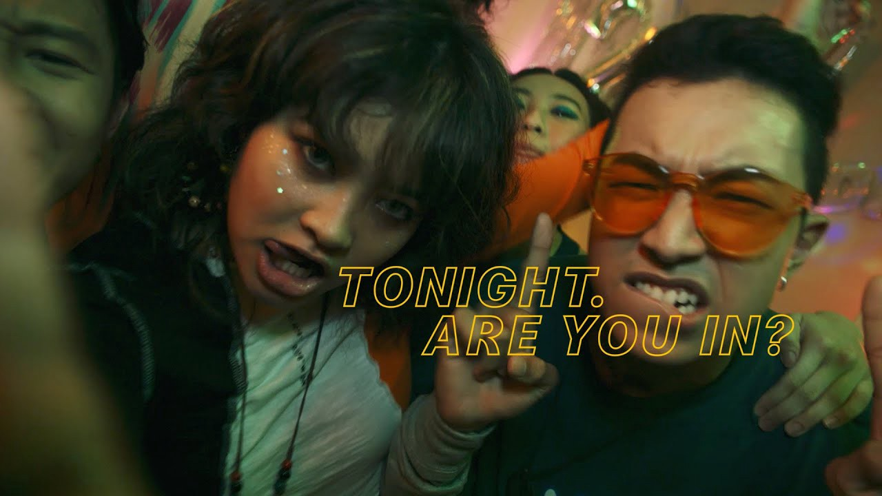"""Text: """"Tonight. Are you in?"""" Young people making faces at a party"""