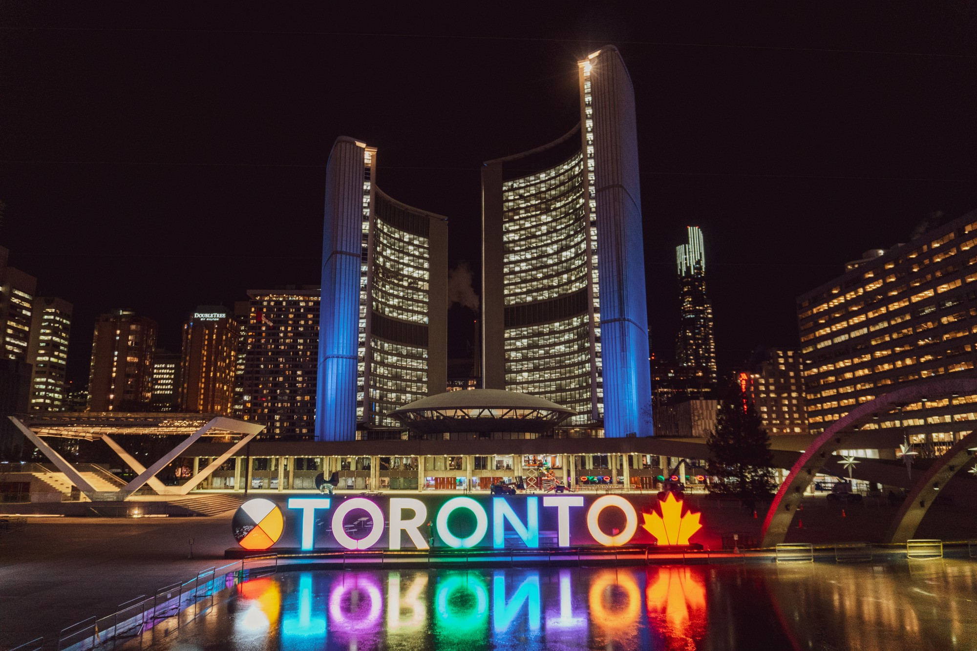 Lit-up Toronto sign in against Toronto skyline at night