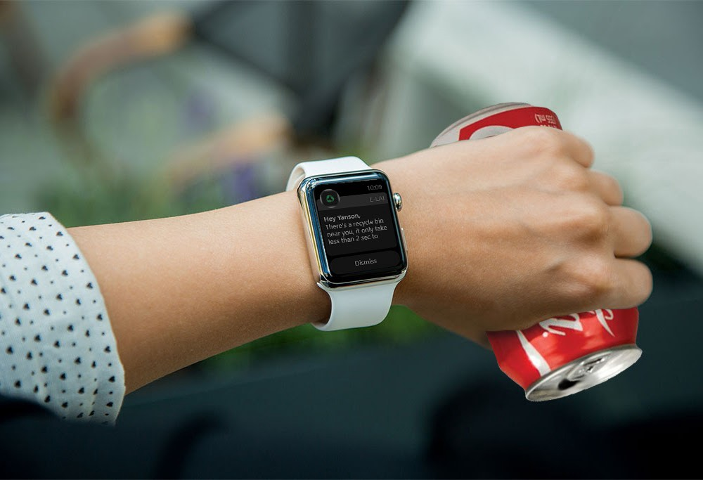 """A woman's hand holding a soda can and wearing a smart watch. The screen of the watch says """"There is a recycling can near you. It only takes less than 2 seconds to…"""""""