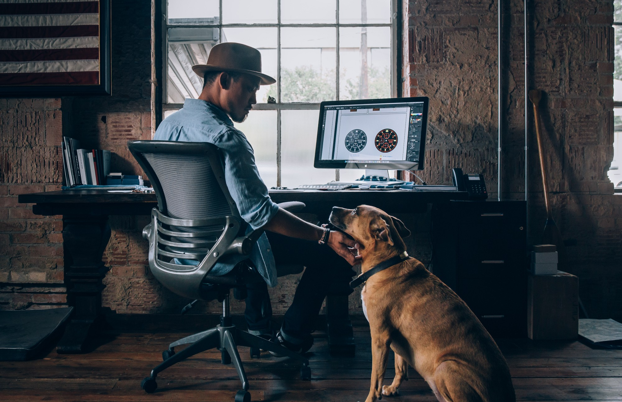 A designer patting his brown dog that is seated next to his desk.