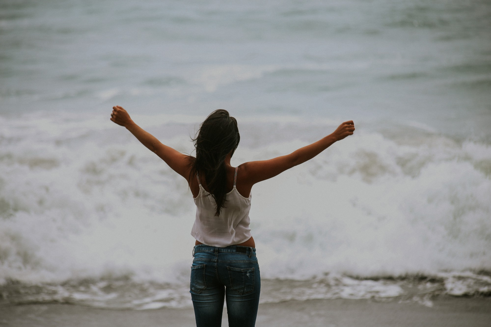 Woman standing on beach in front of waves. Arms open.