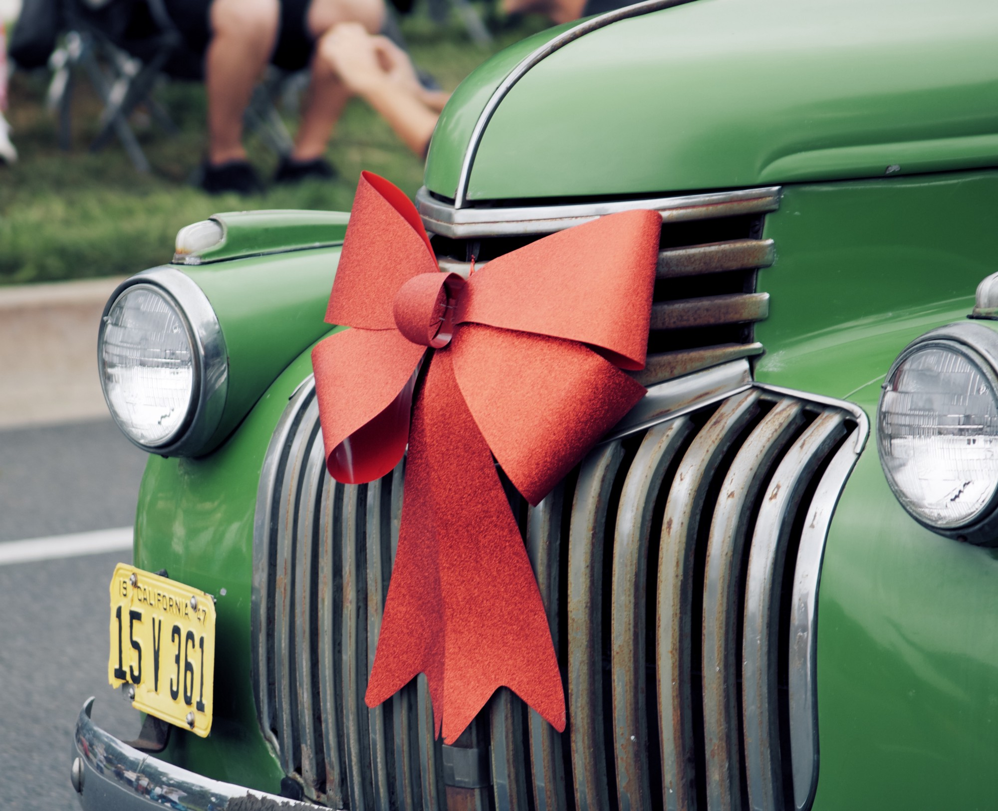 Green car, sporting a big jolly red ribbon of hope. Hope — we need it in all our endings and beginnings.