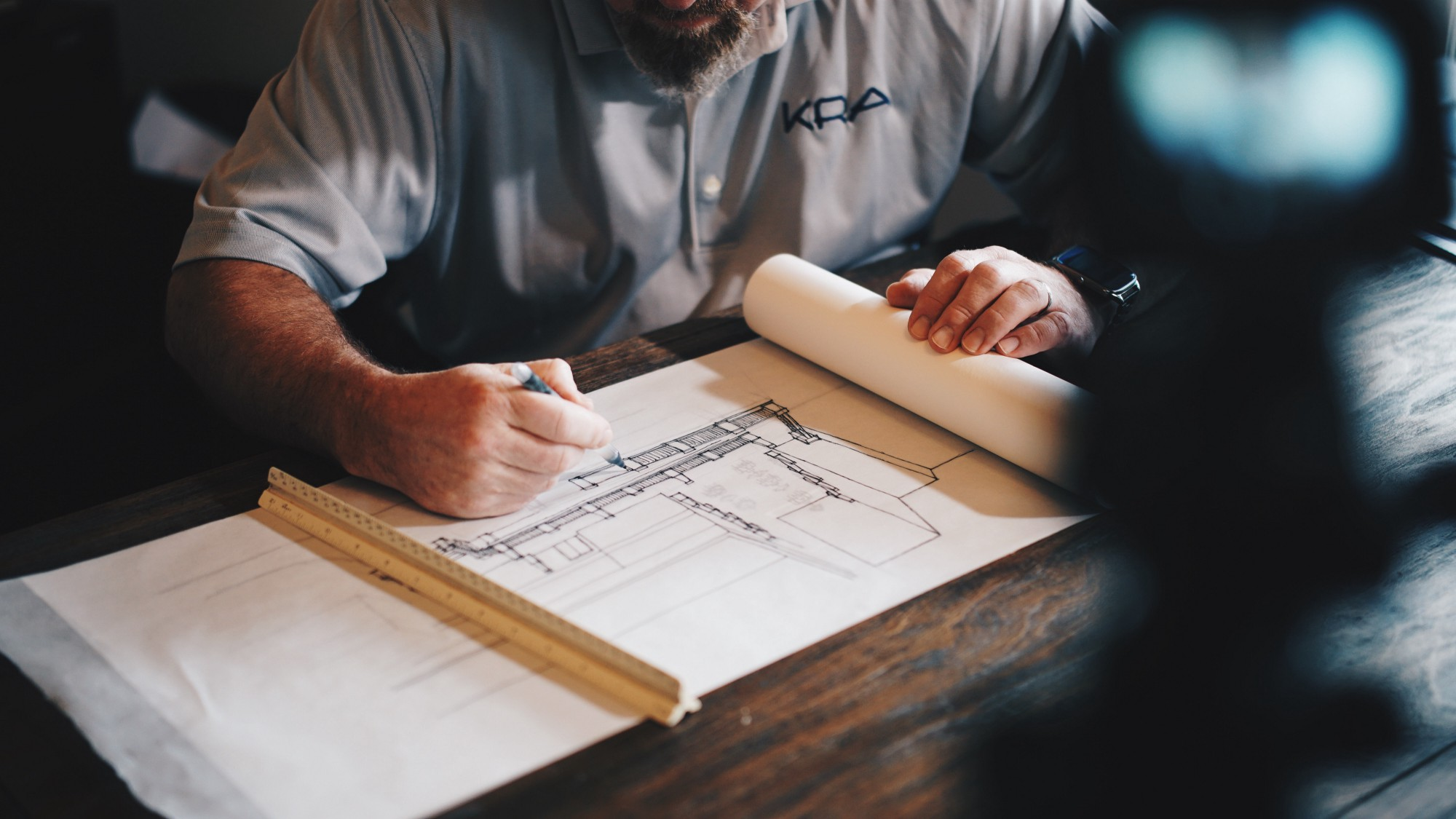 An architect at work sits at a wooden desk drawing a sketch.