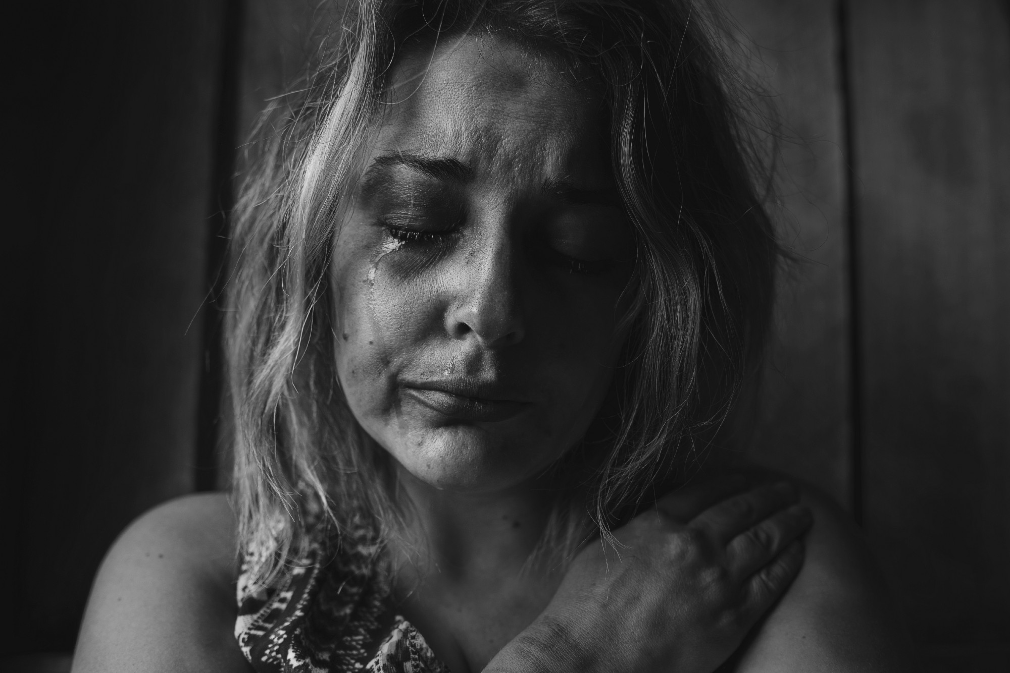 Black and white image of woman with long hair, downcast eyes, and tear streaked face