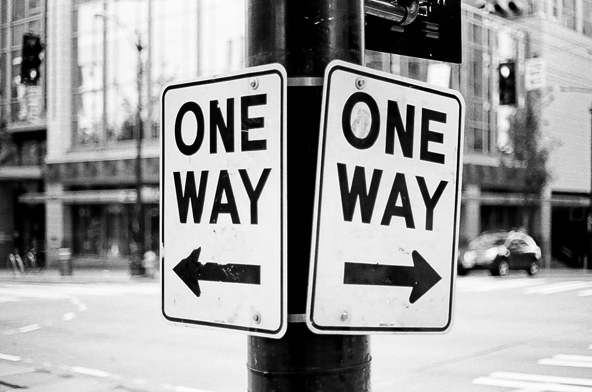 """Two """"One Way"""" road signs pointing opposite directions."""