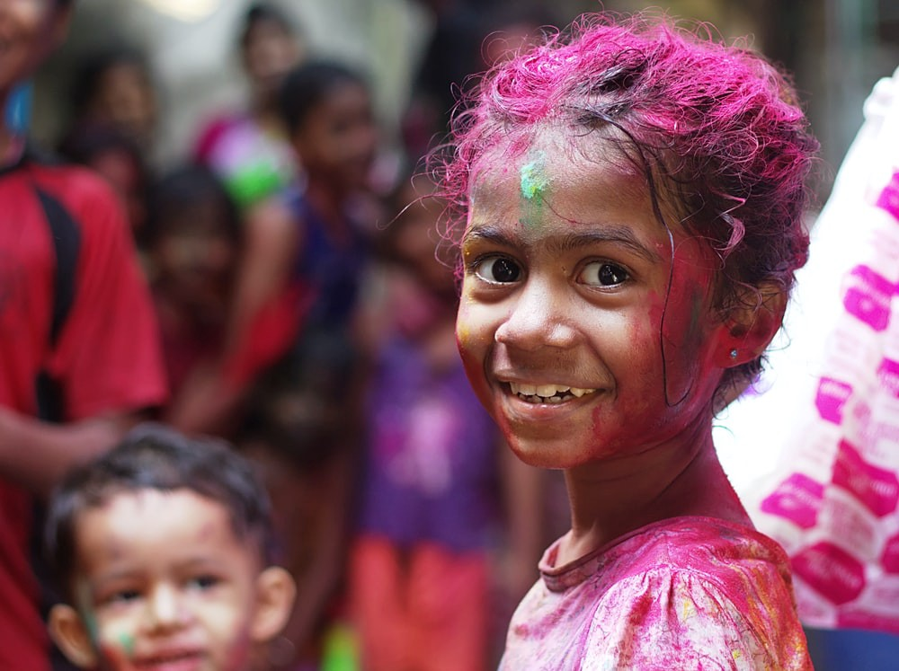 A small Indian girl all covered in paint