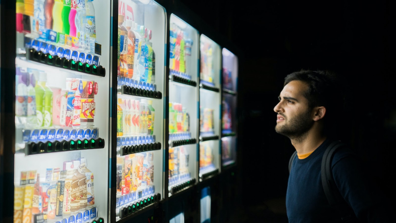 A man choosing a drink from 5 different Japanese vending machines