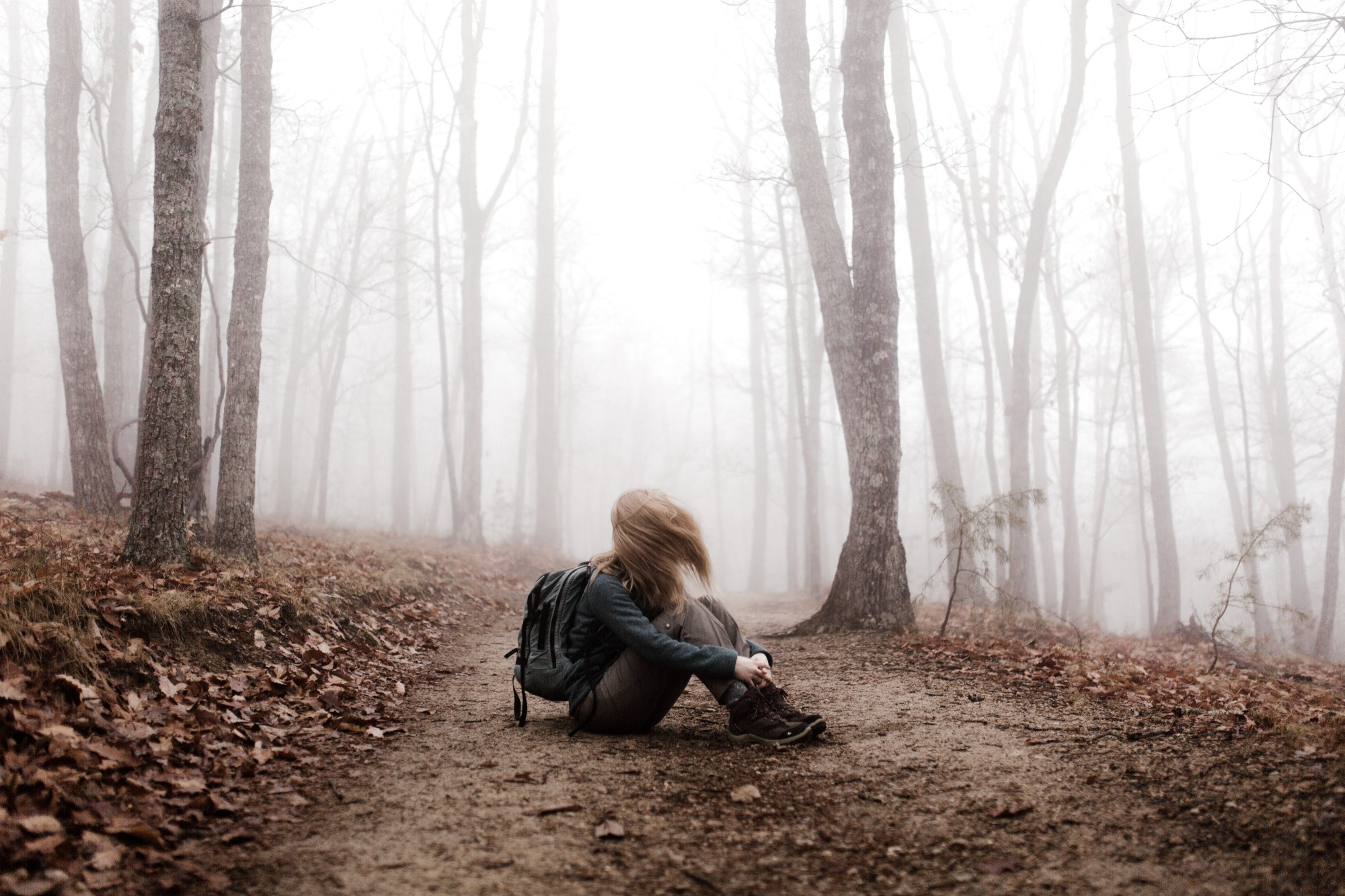A girl on a hiking trail, sitting down, holding her legs, sad.