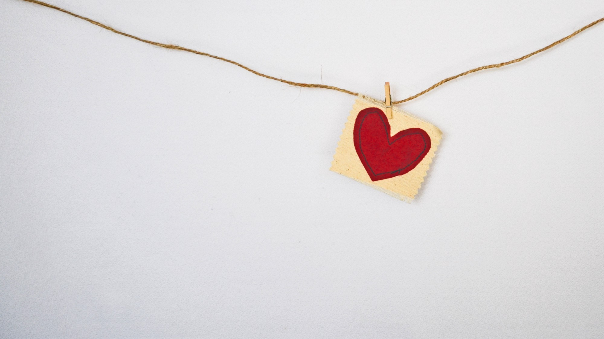Photo by Debby Hudson on Unsplash—an image of twine with a red heart clothes pinned to it on a blank white wall