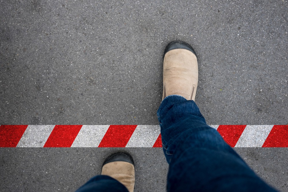 Image of a person's foot in a closed brown show crossing a red and white line to indicate crossing of boundaries and not respecting consent.