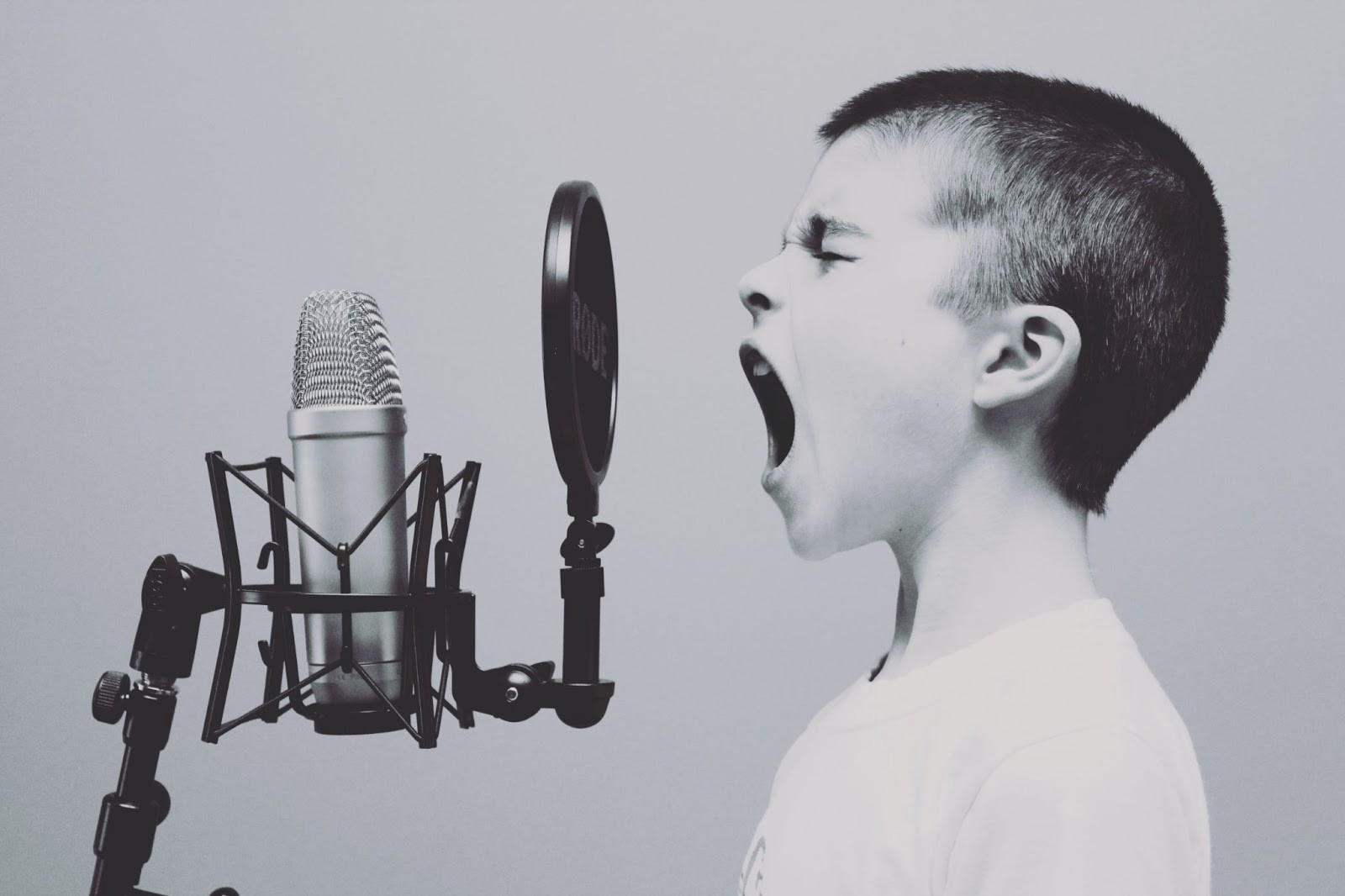 Black and white photo of a young boy with short hair screaming into a large microphone.