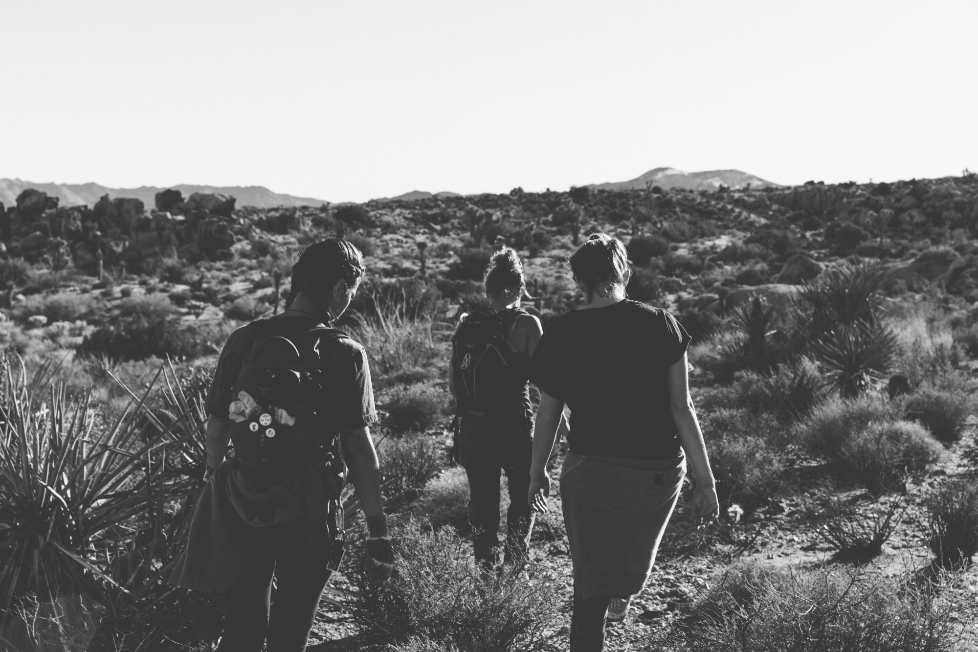A black and white image of three people walking up an arid hillside.