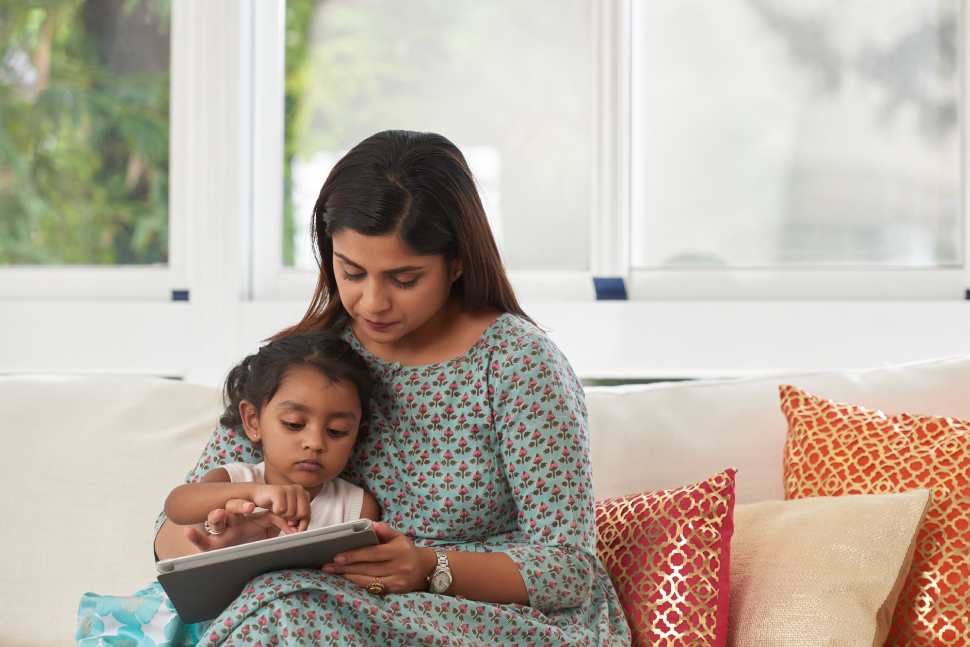 A mother holds her young daughter while they read together.