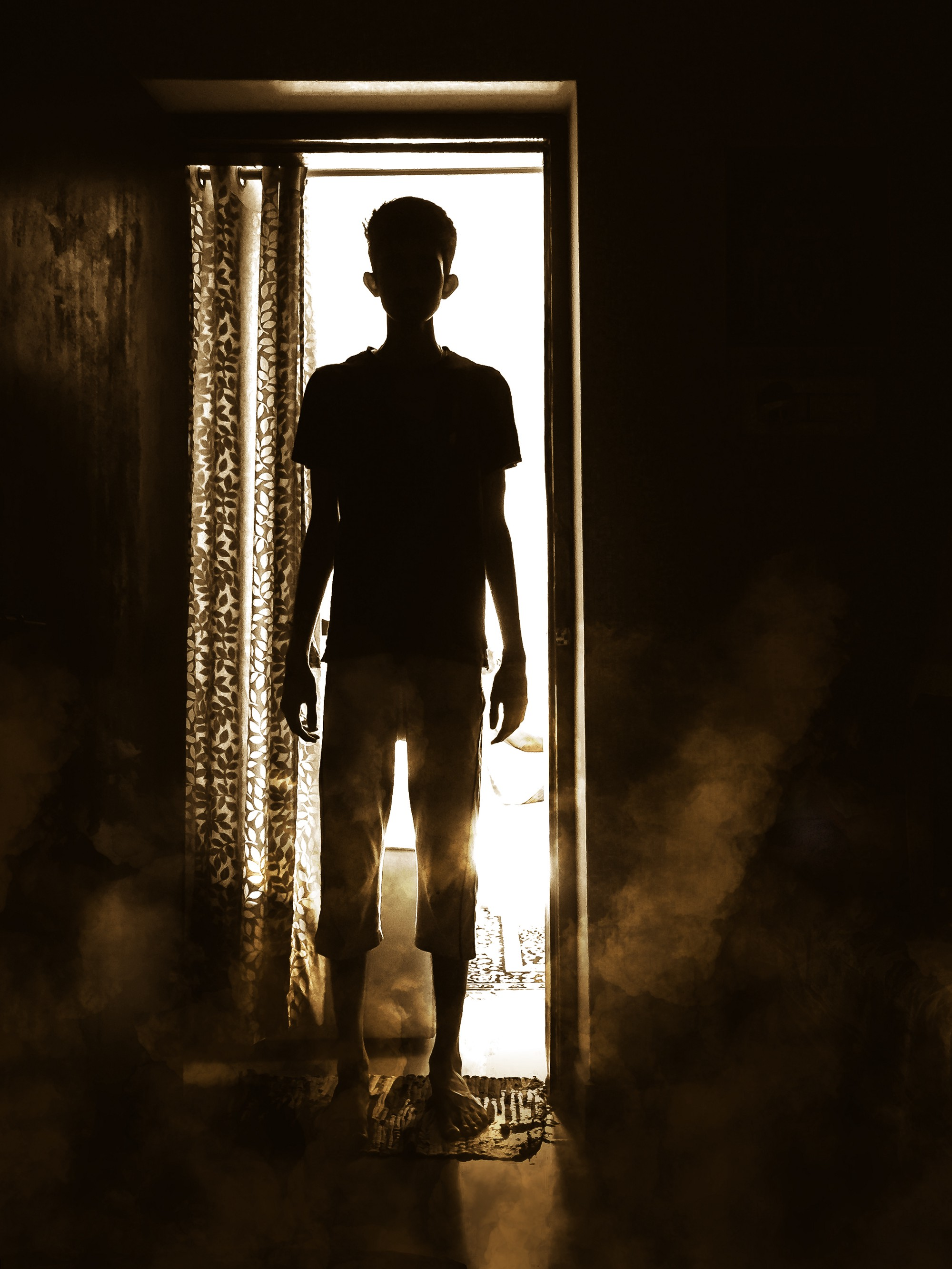 The dark silhouette of a child in a doorway.