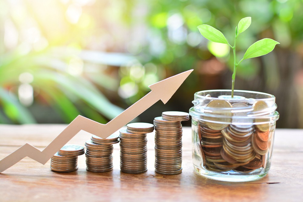 Image showing stacks on coin increasing in size and then becoming a jar full of coins with a plant growing from it. There is an arrow to indicate the jagged growth that takes place when money compounds.