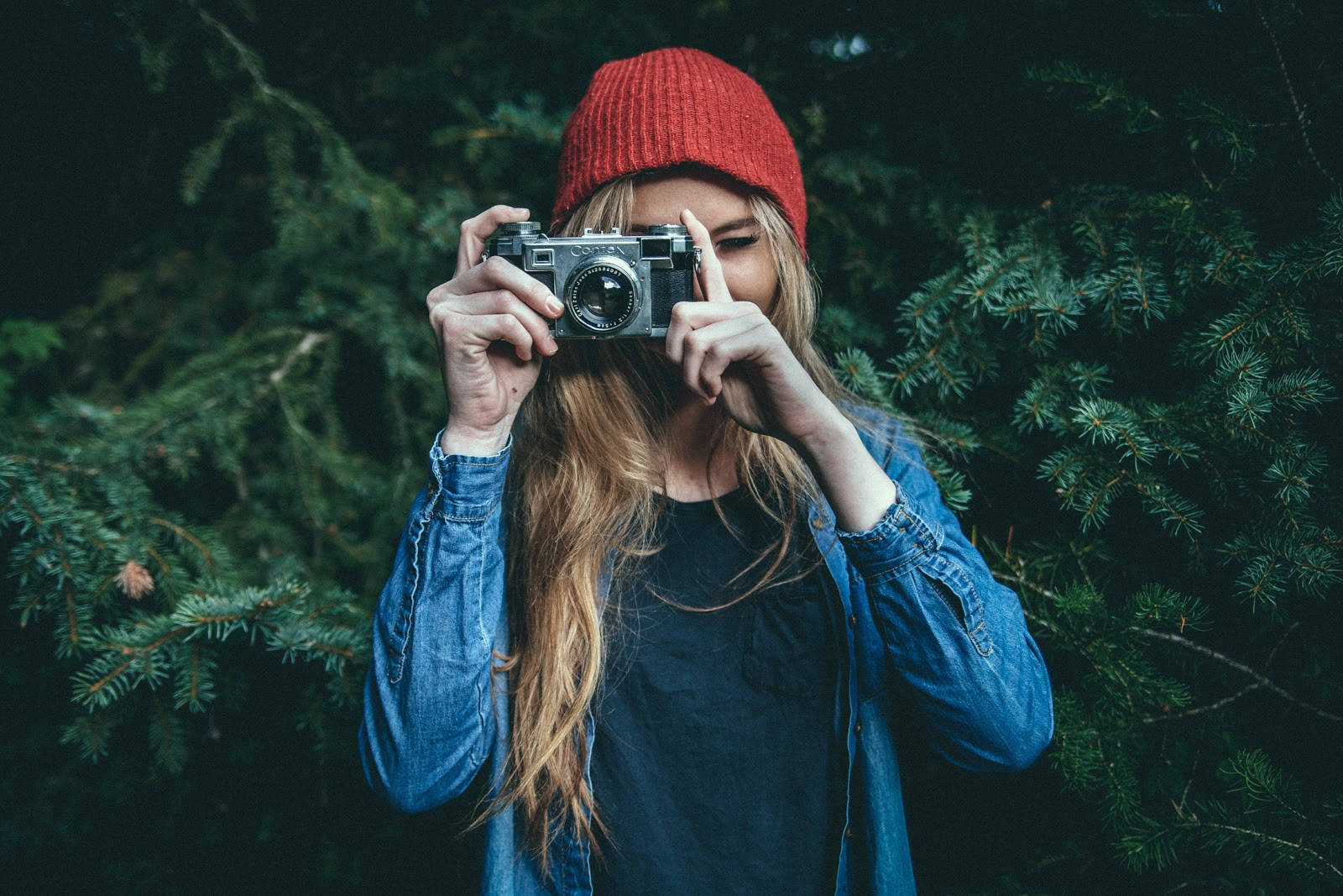 Girl wearing a denim jacket and red hat holding vintage camera with pine trees in the background.