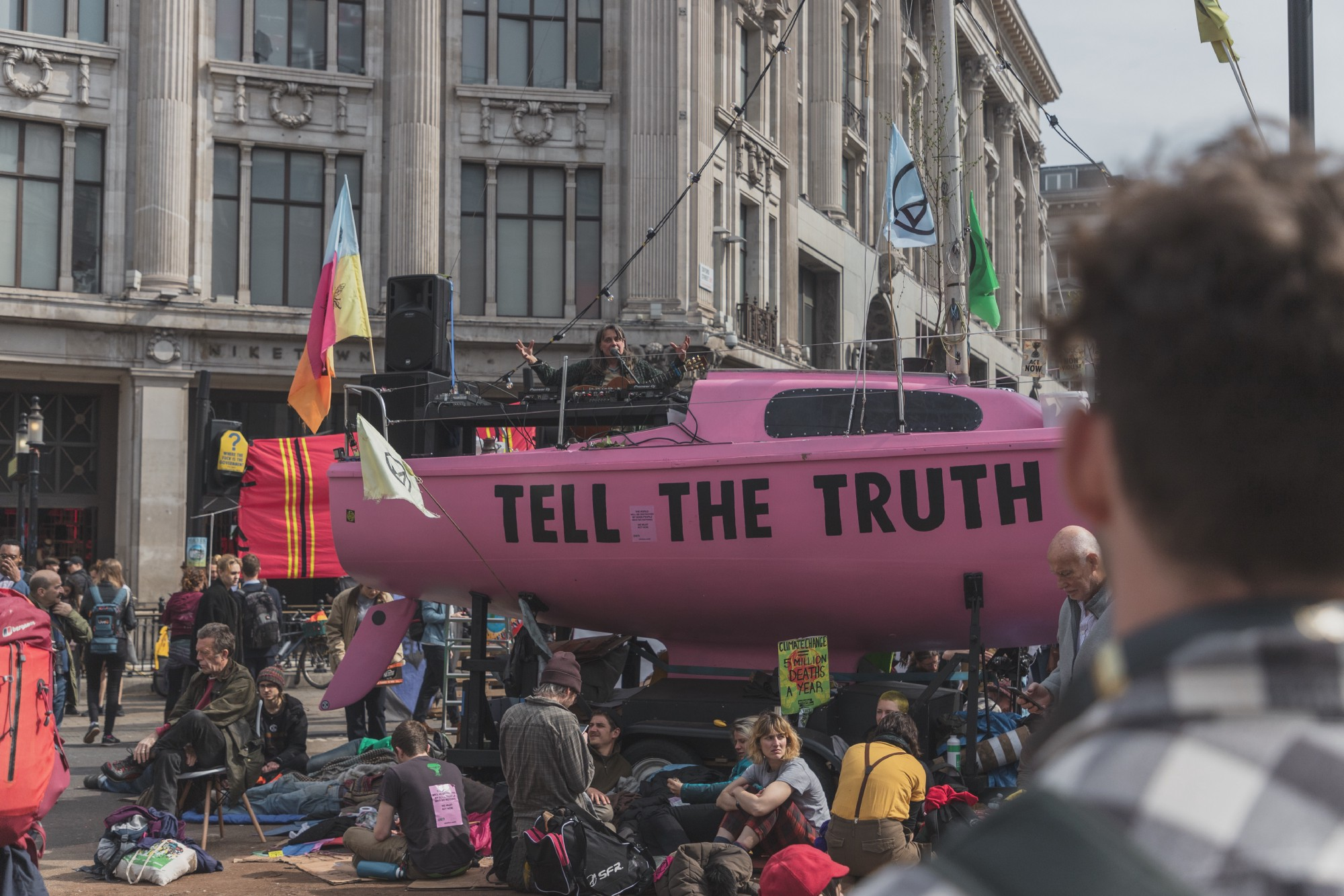 In front of an office building protestors sit in front of a pink water vessel with 'tell the truth' in large black letters.