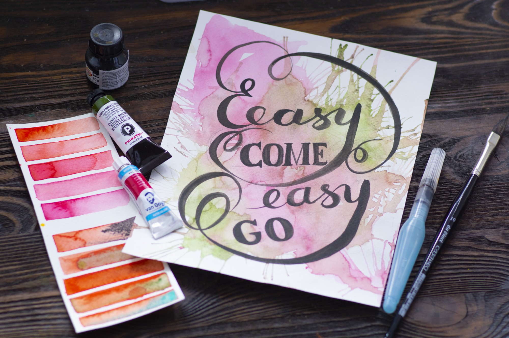 A poster with markers on a wooden table that says Easy Come Easy Go
