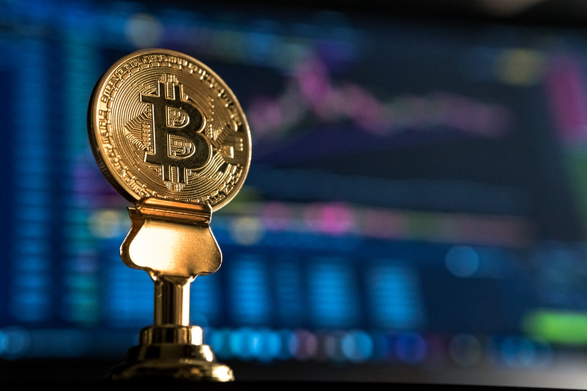 A Bitcoin sits on desk with stock charts in the background