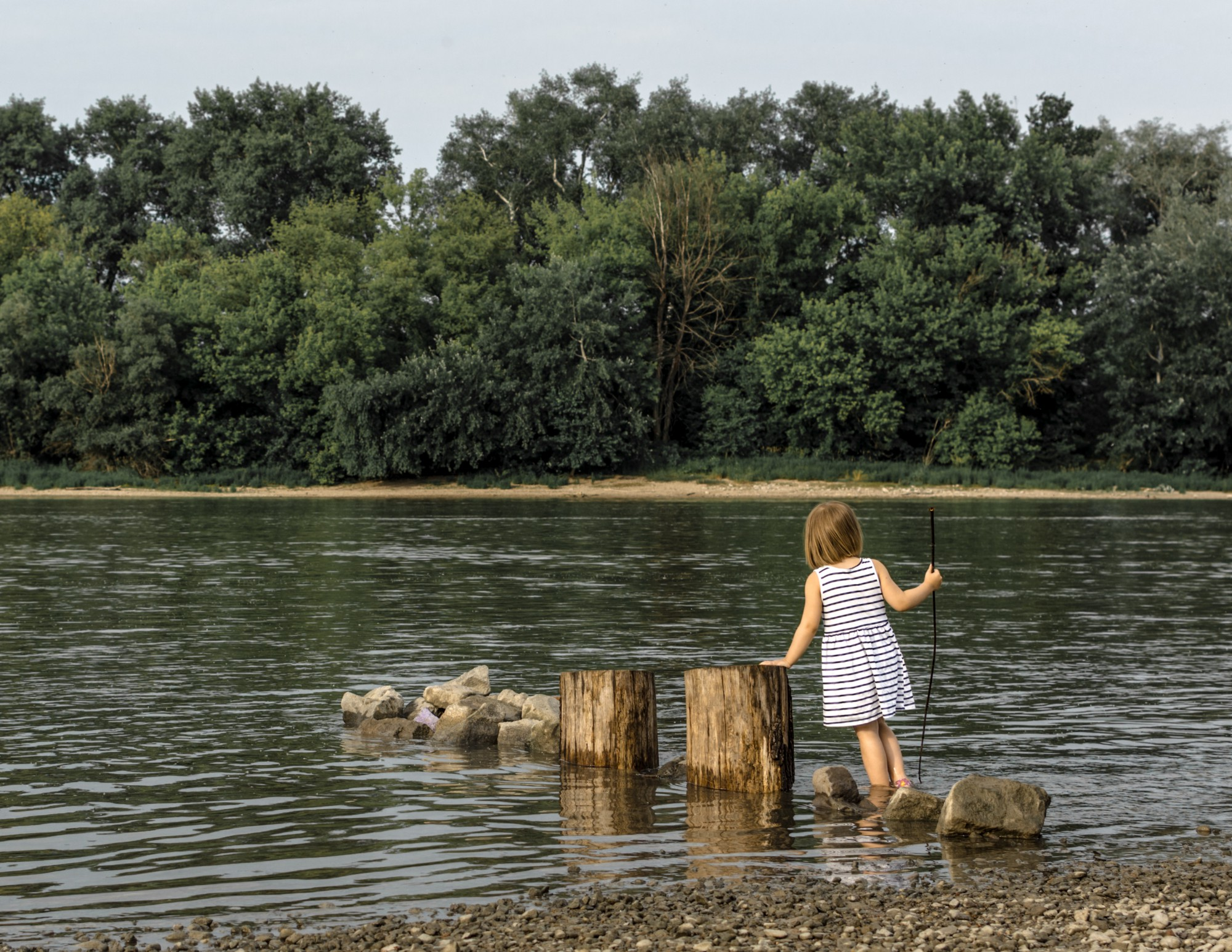A young girl playing by the lake