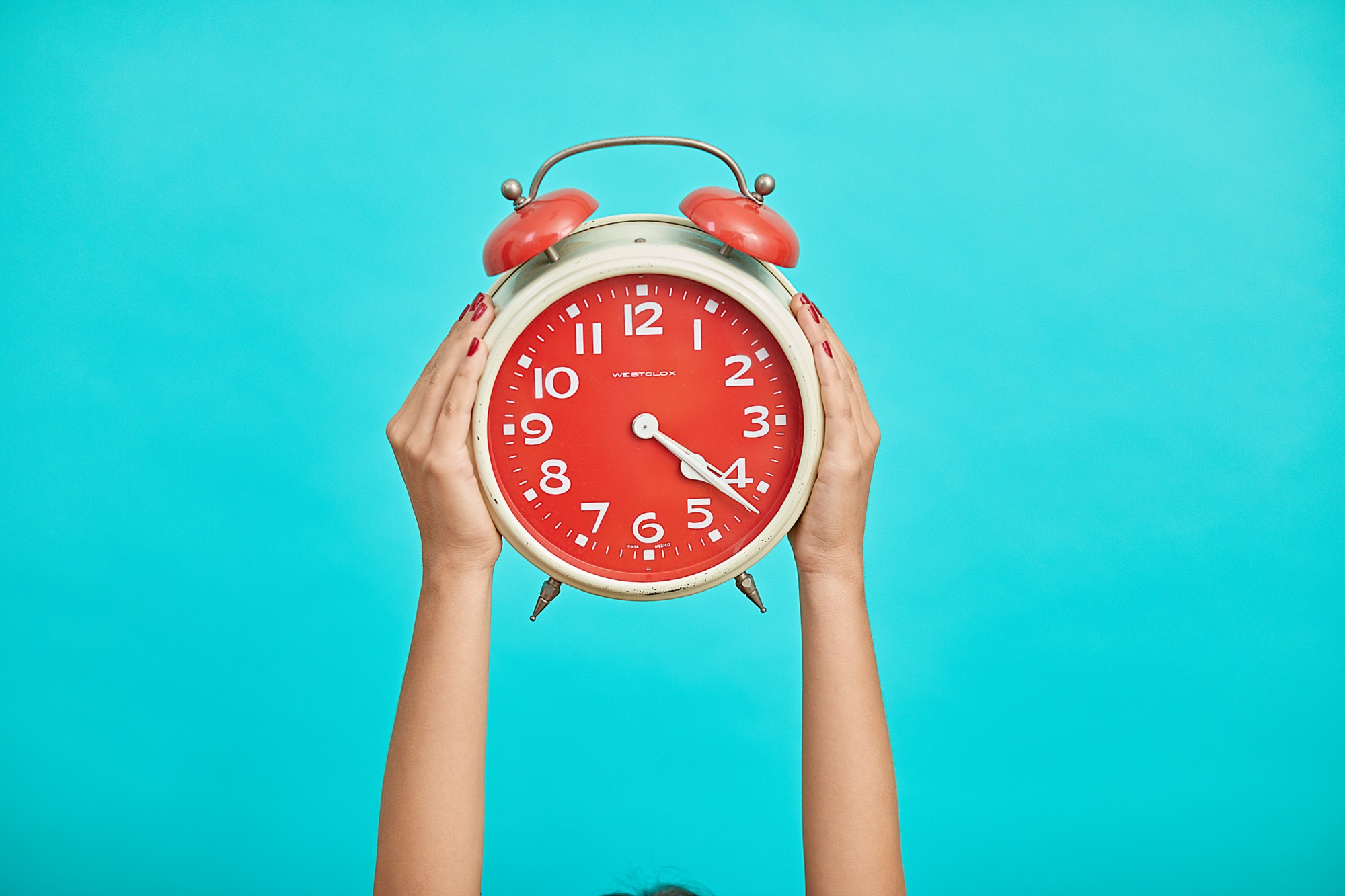 Woman holding alarm clock in the air