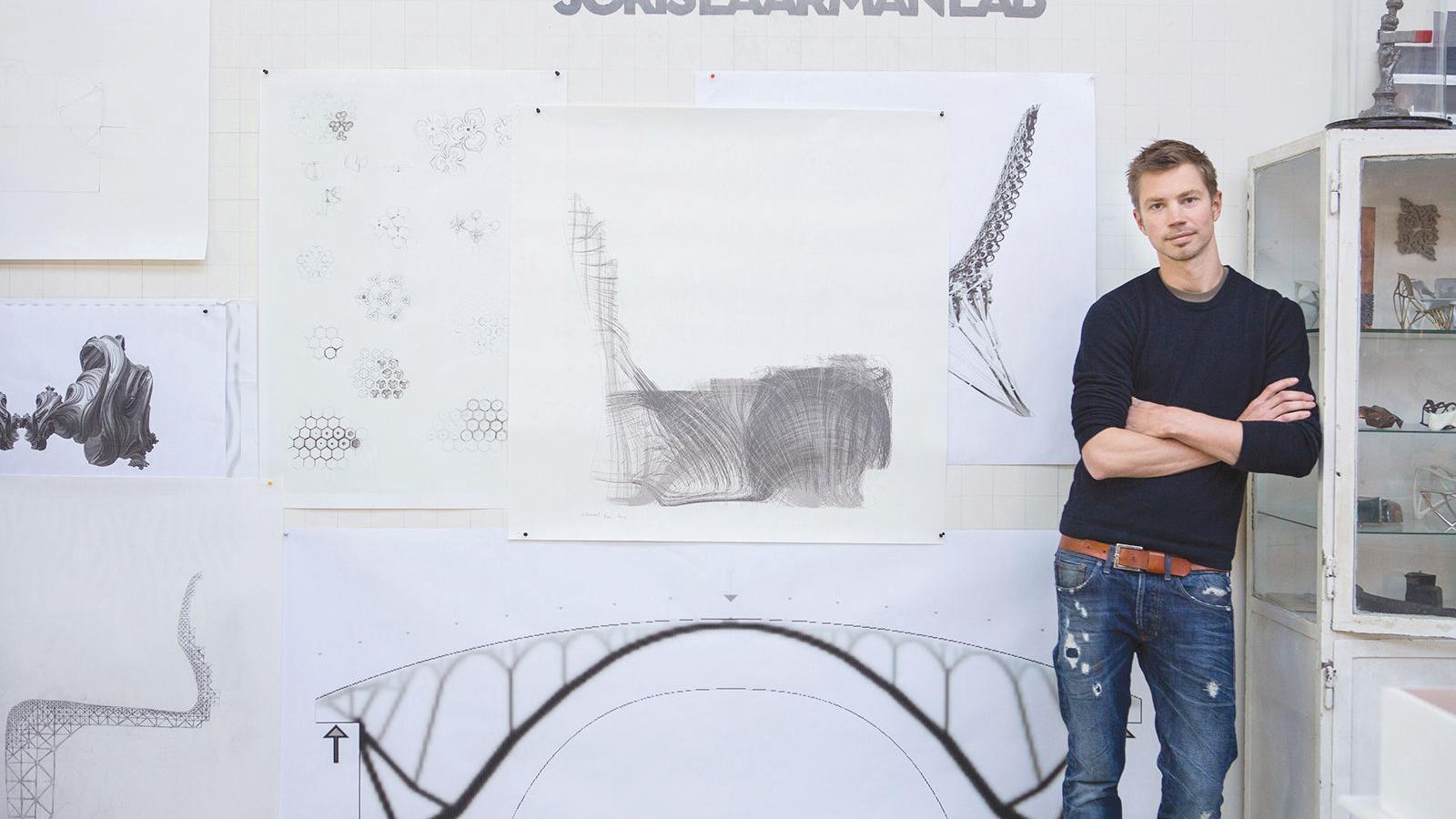 """Joris Laarman stands with his arms folded against a wall of sketches and inspiration under a sign that reads """"Joris Laarman Lab."""""""