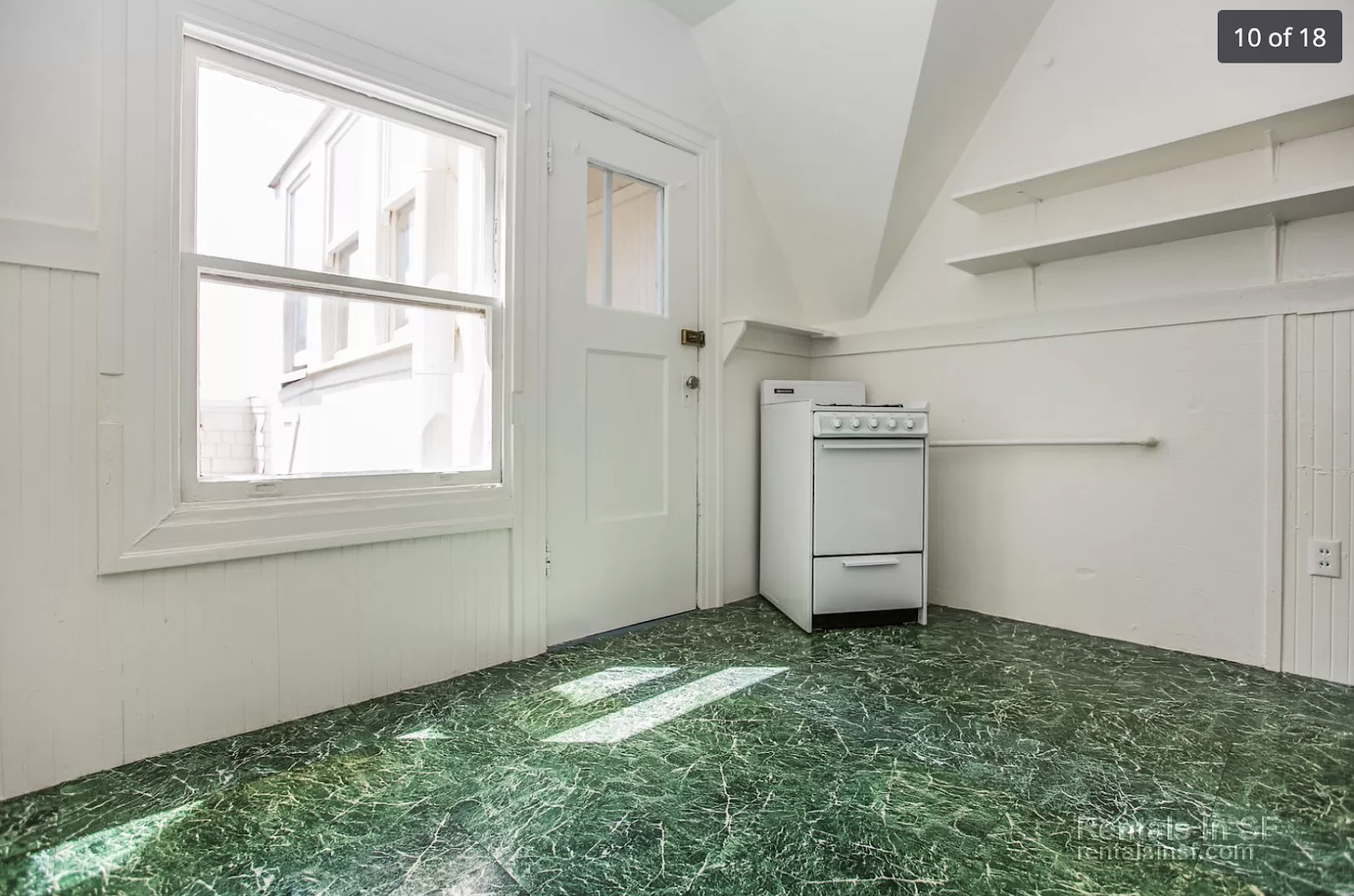 A white oven awkwardly placed in the corner of an otherwise empty room with green vinyl flooring.