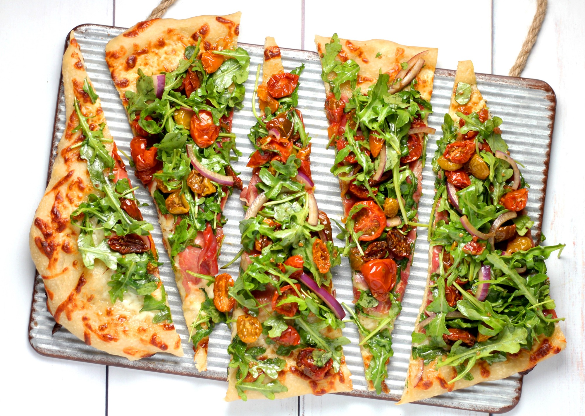Slices of homemade pizza topped with tomatoes, vegetables, and leafy greens.