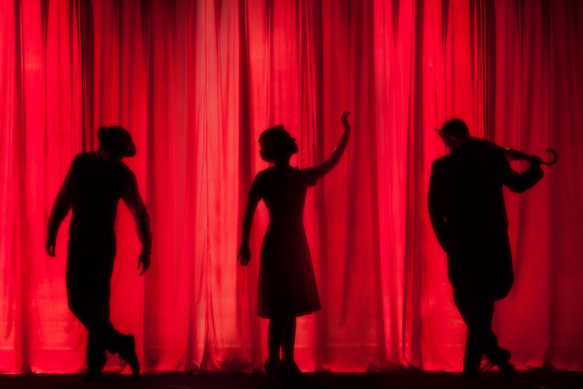 three black silhouettes against a red drapery background