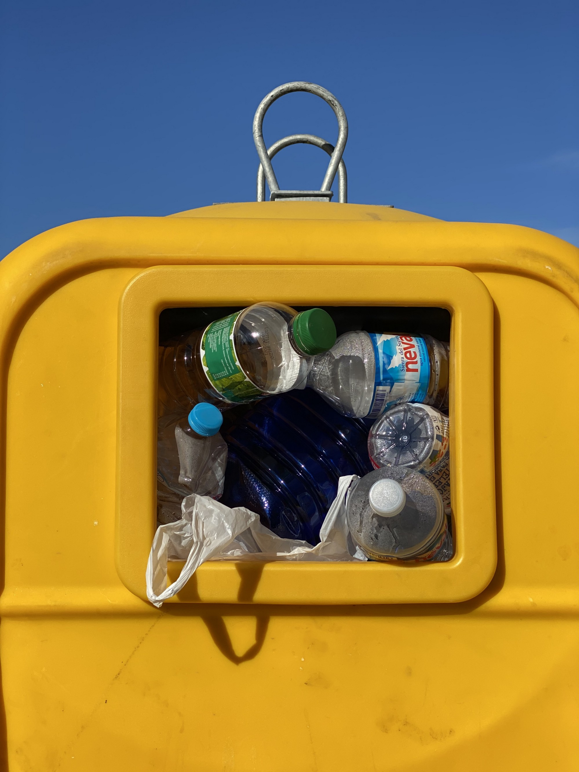 A bright yellow trash can filled with empty plastic bottles and plastic waste.