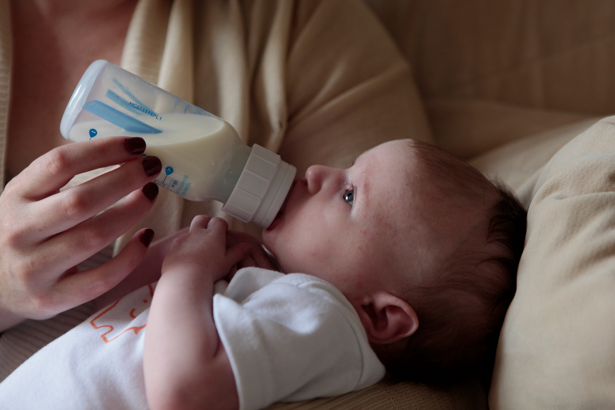 A mother embracing her baby while feeding her a bottle of formula.