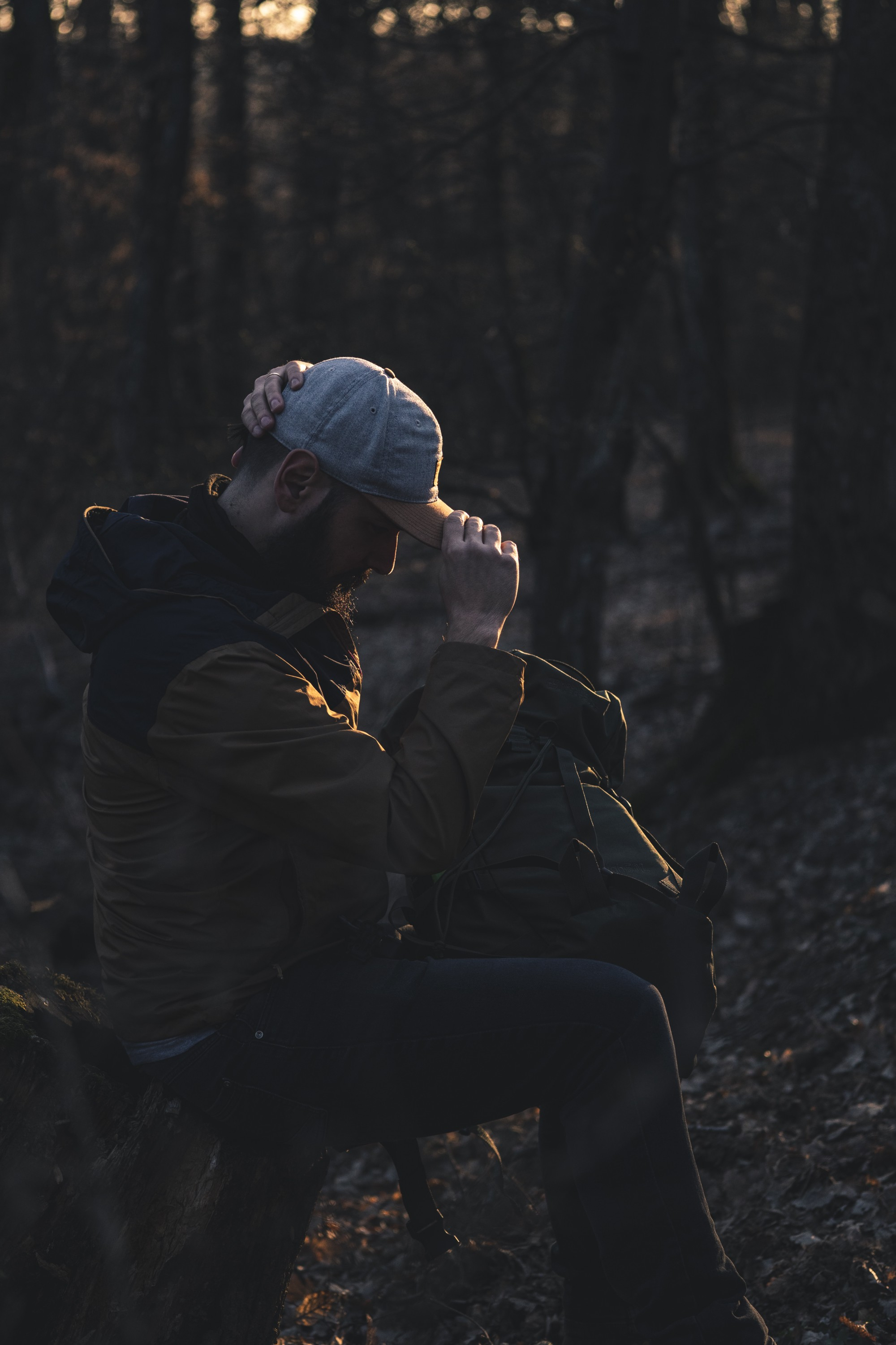 A man sitting in the woods with his head bowed. He is wearing a baseball cap.