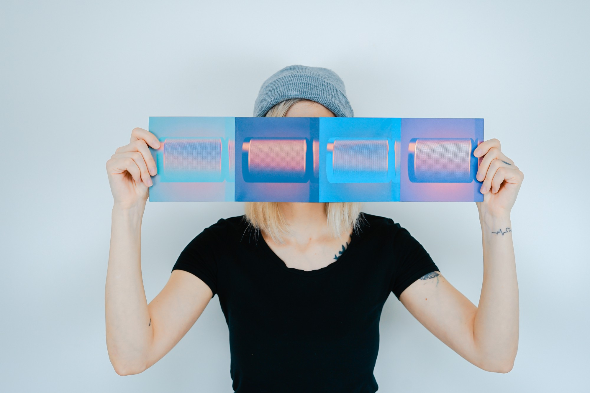 A woman hides her face behind a screenprint.