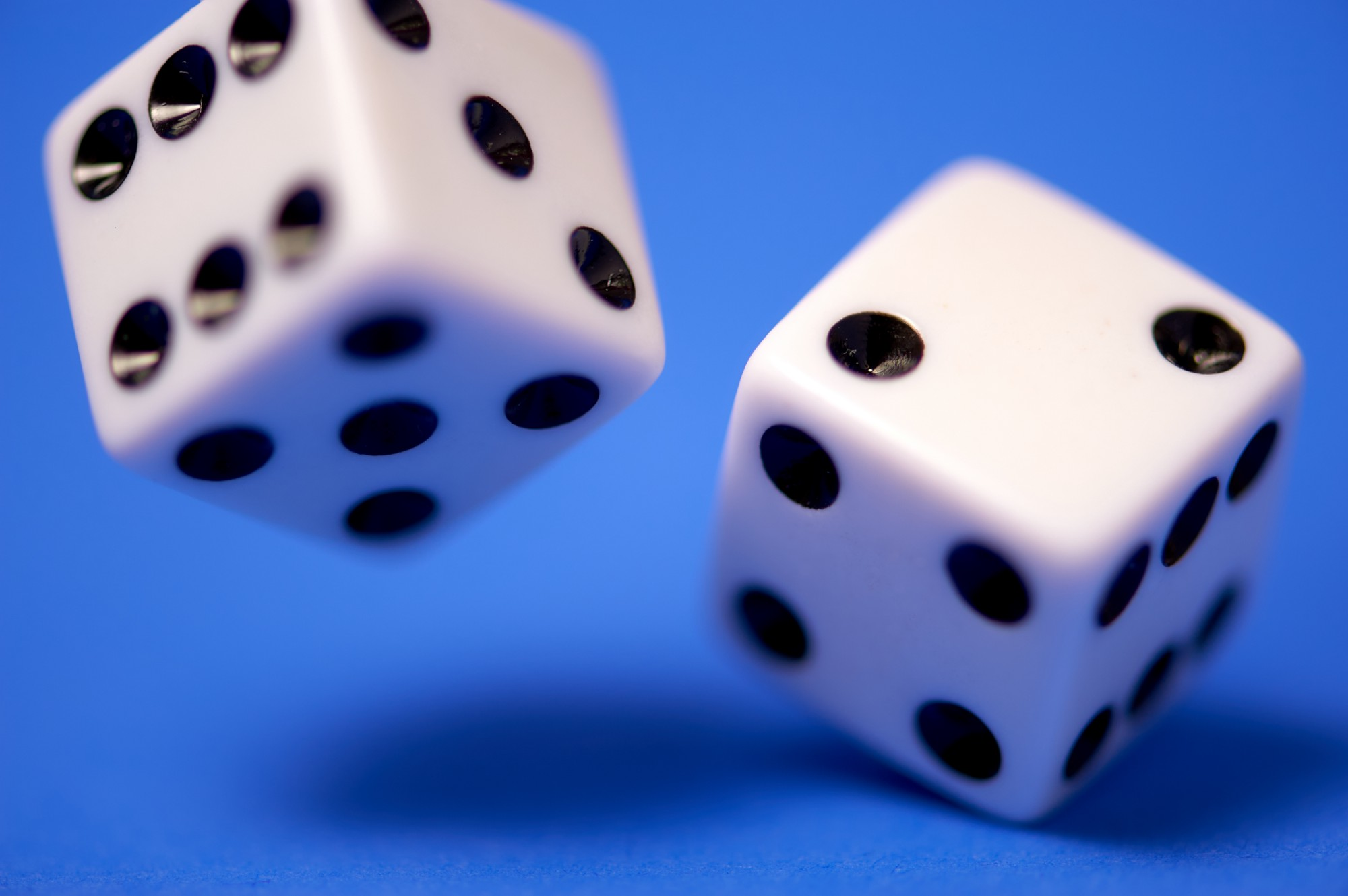 Two dice rolling on a blue table
