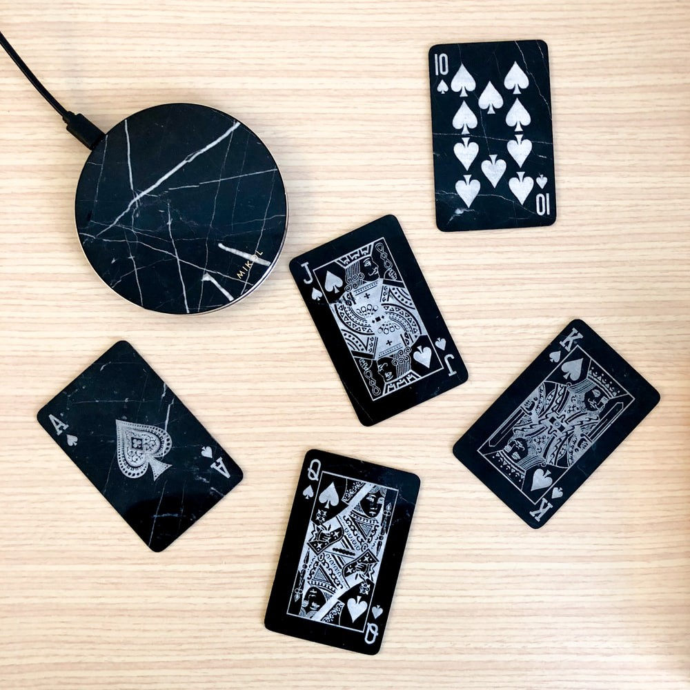 Black wireless charging pad on a wooden surface with playing cards