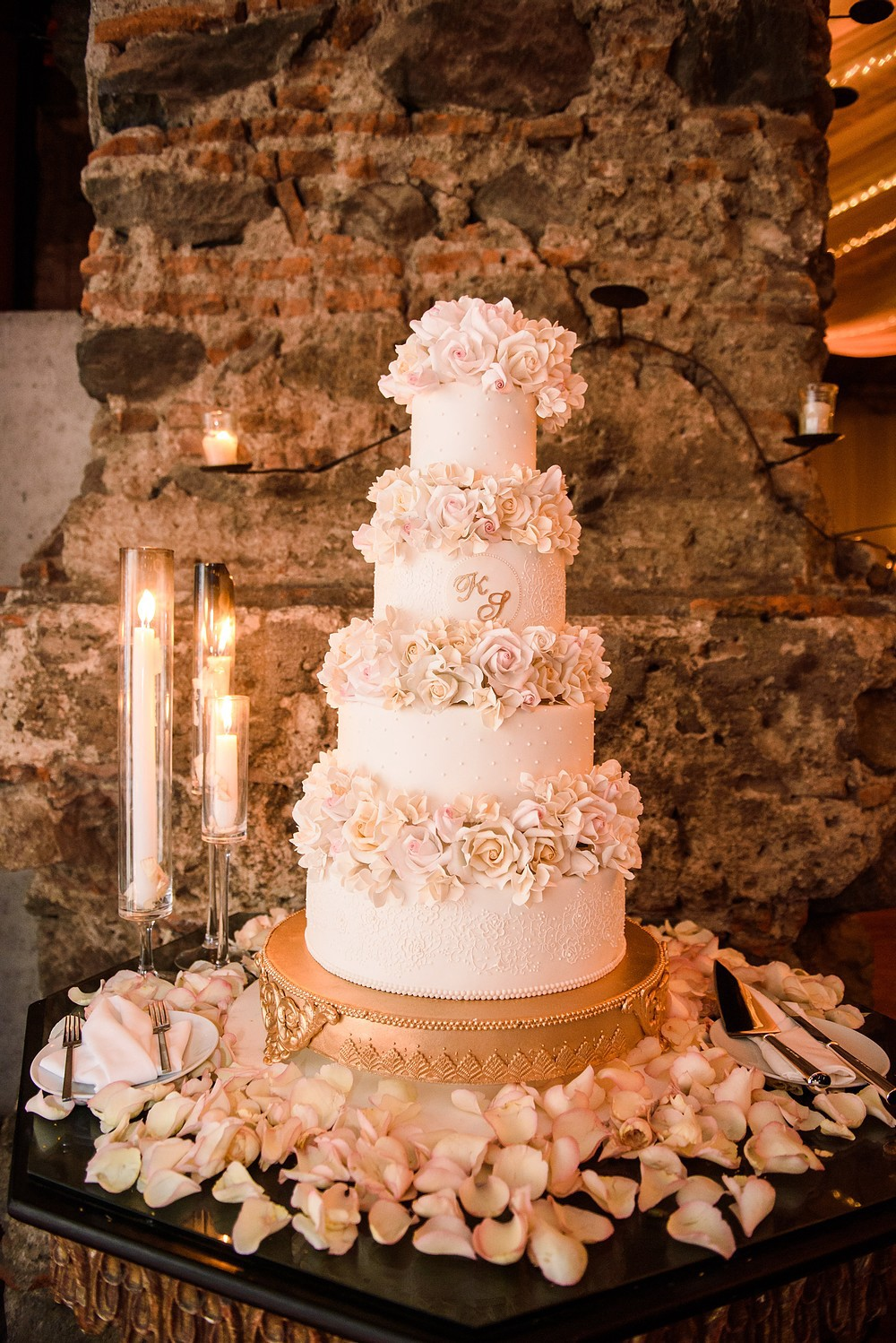 A white 4-tier wedding cake with fondant flowers between the tiers. Sitting on a golden cake stand, surrounded by candles.