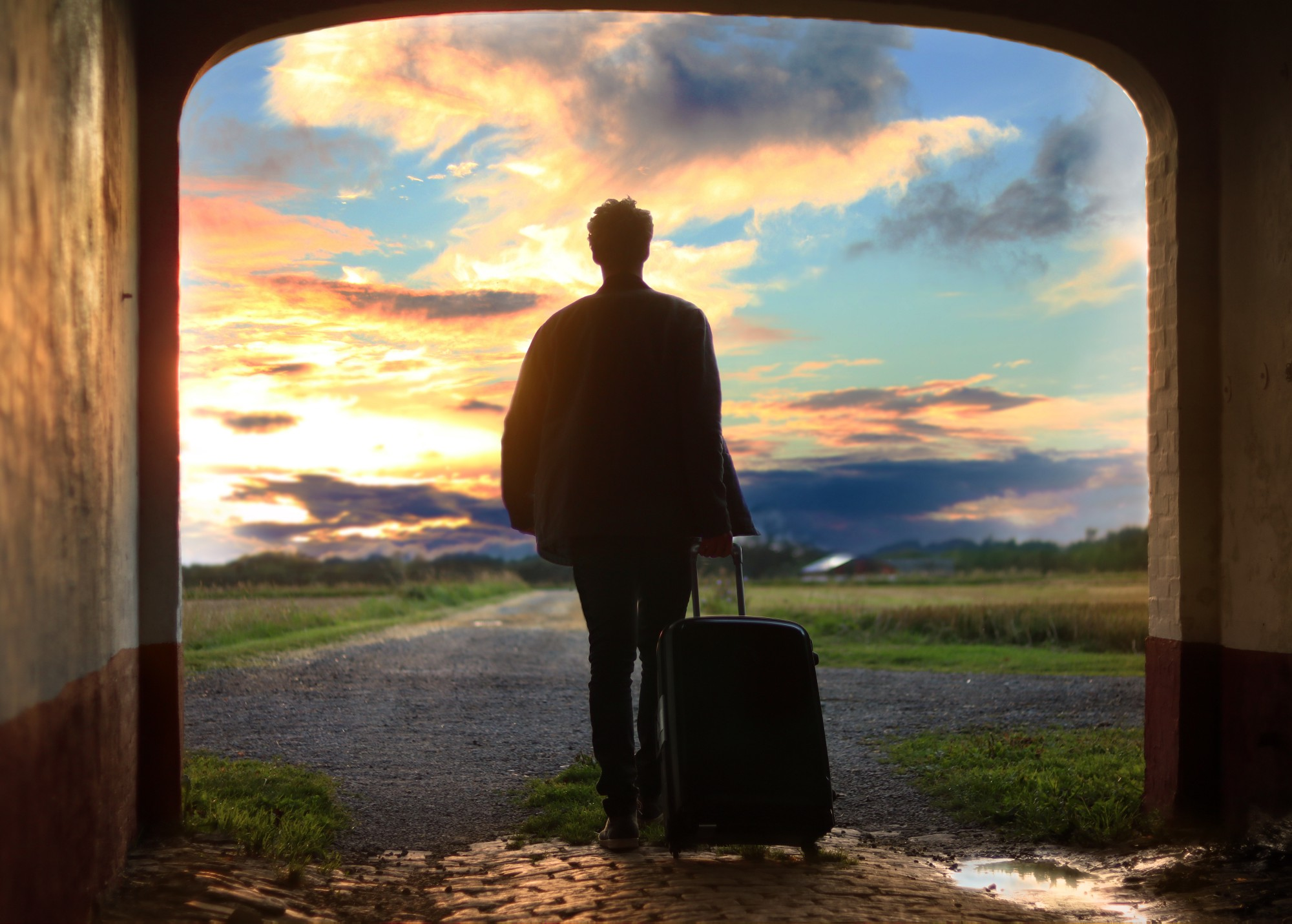 Man with suitcase and sunset