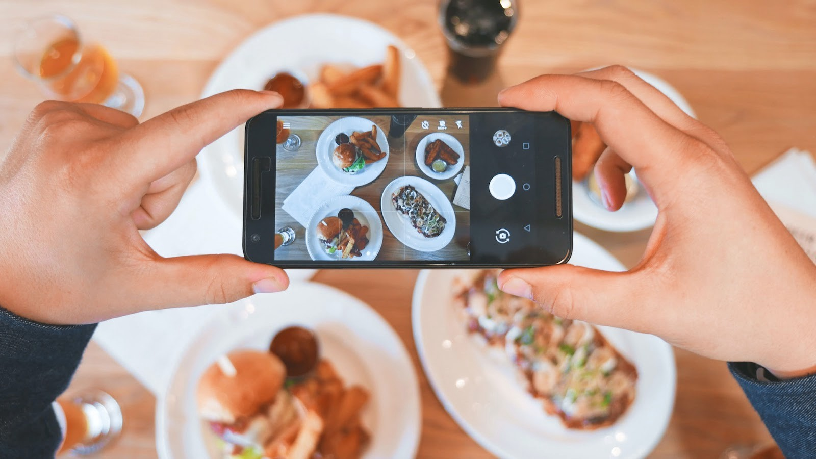 A person holds a camera phone on a Western meal about to take a photo