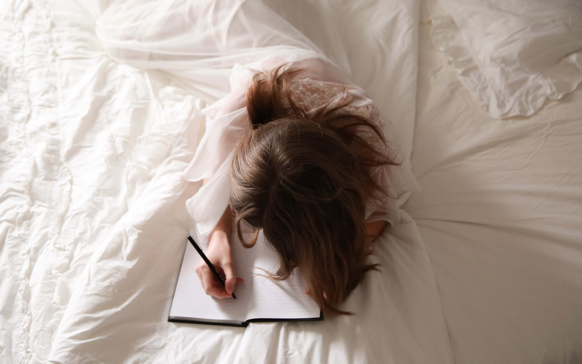 A woman lays in white sheets, writing a letter.
