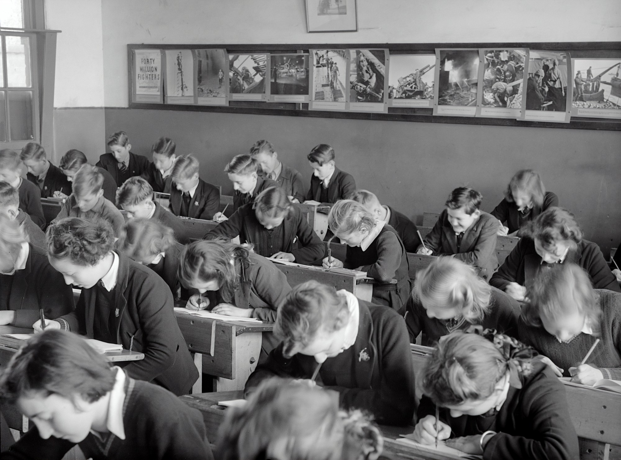 Black and white vintage photo of many uniformed pupils hard bent over desks at school.