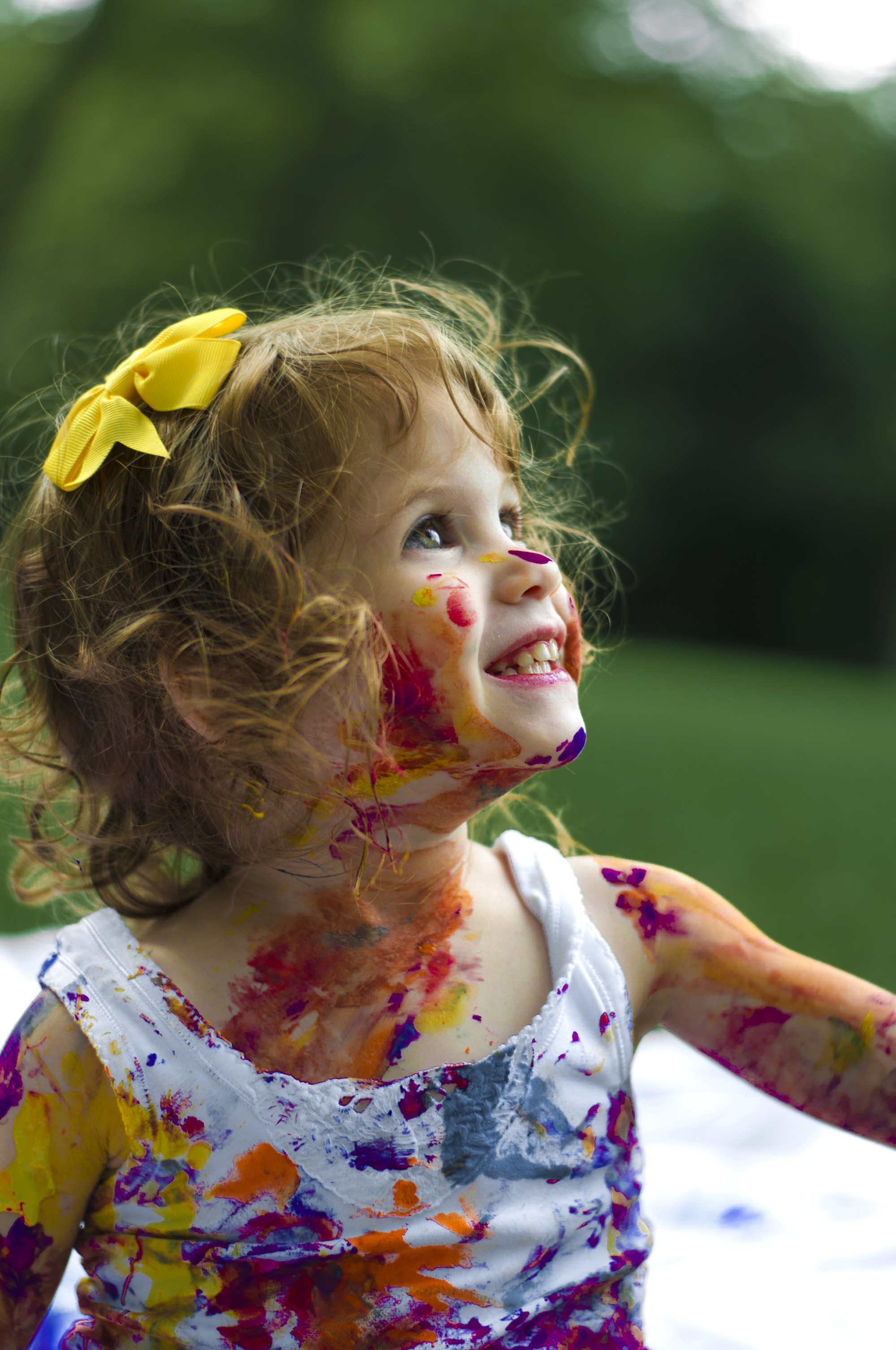 Little girl with big smile, standing, looking up. Colorful paint splotches all over her face and white dress. She looks happy